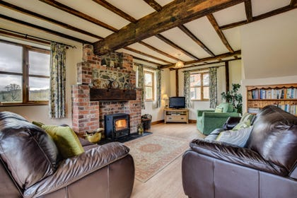 Large spacious oak beamed lounge with warm, welcoming log burner