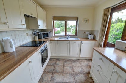 The lovely fitted kitchen has ample storage units and provides a well-equipped space for guests to prepare meals
