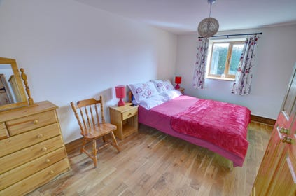 Attractive, spacious king-size bedroom with oak floor and quality furnishings