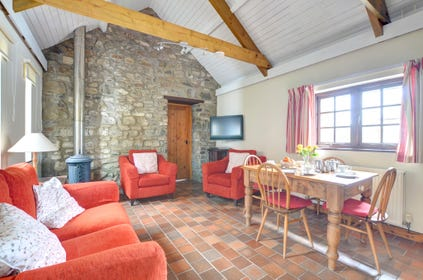 The living room has rugs over quarry tiled flooring, dining table and four chairs, comfortable three piece suite and a woodburning stove