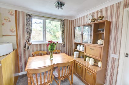 The dining area, to one end of the kitchen, has table and four chairs and a sideboard unit
