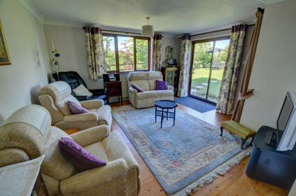 The comfortably furnished sitting room has patio doors leading out to the enclosed garden