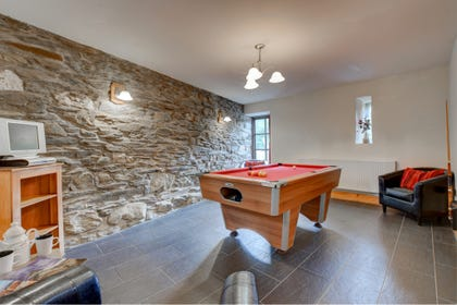 Games room offers a separate living area with leather chairs & TV