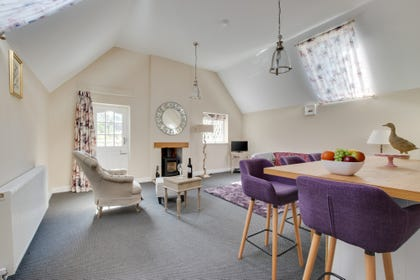 Stylish open plan kitchen and living area with wood burner