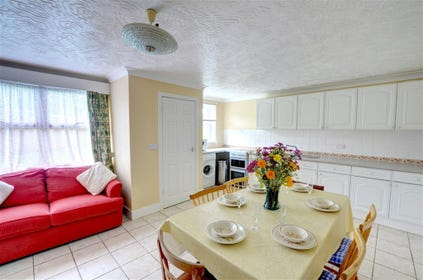 Very spacious fitted kitchen with dining table and a sofa