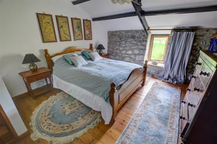 This charming double bedroom has a large pine bed and is furnished in character
