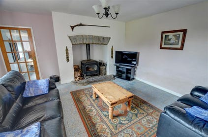 The first sitting room has a TV, large woodburning stove in the fireplace and a DVD player