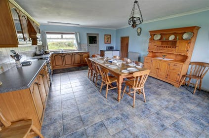 Large kitchen/dining room with fitted oak units, dishwasher and large dining table with 8 chairs