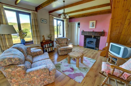Lovely bright and spacious lounge/dining room with beams, large oil-fired stove in fireplace and sofas