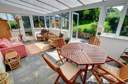 Large conservatory with sofa, cane chairs, dining table and 4 chairs, and doors to the patio and garden