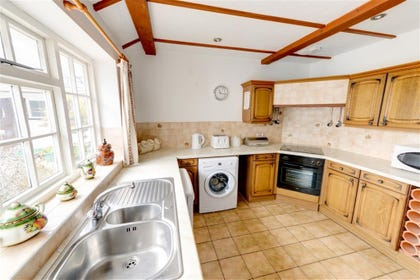 The fitted kitchen has a tiled floor and beamed ceiling