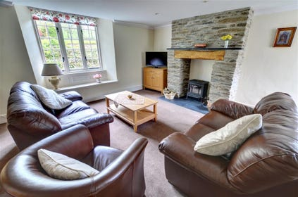 The spacious sitting room has comfortable leather seating and a cosy woodburning stove in the stone fireplace