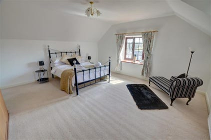 The spacious double bedroom has an attractive 'Victorian' bedstead and chaise longue