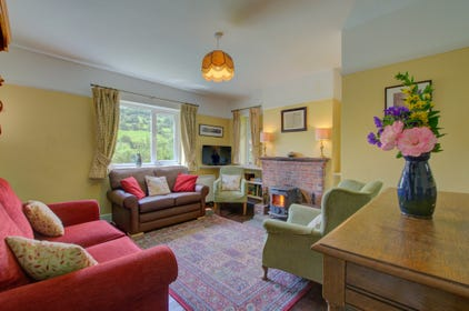 The cosy sitting room has an open fire and is furnished and decorated in traditional style