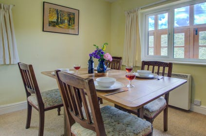 The dining room has an oak extending dining table and six chairs, and windows to two sides