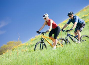 Couple mountain biking through the luscious grass of North East Wales